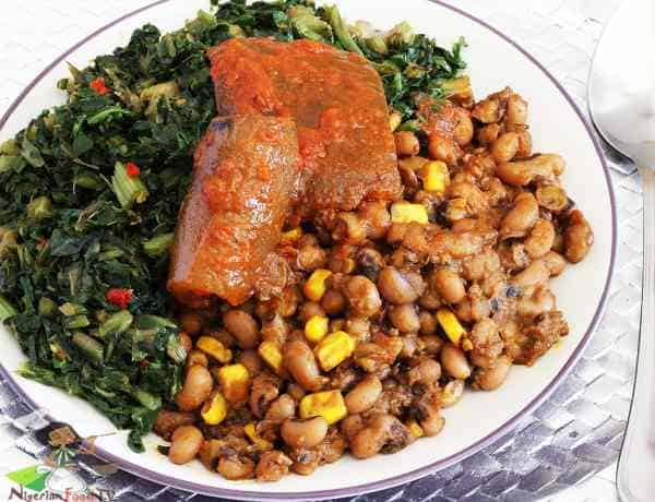 Nigerian beans and corn adalu with steamed vegetables