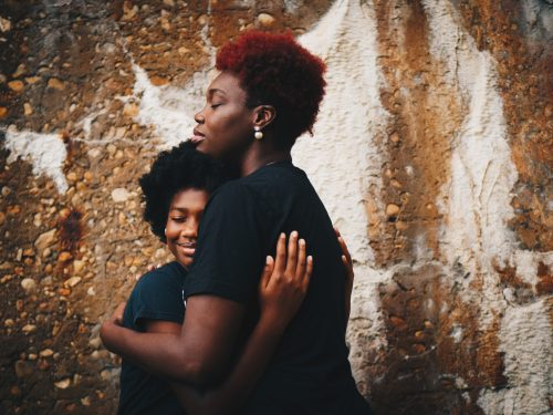 This picture shows a mother showing solidarity and love to her child by hugging her tightly